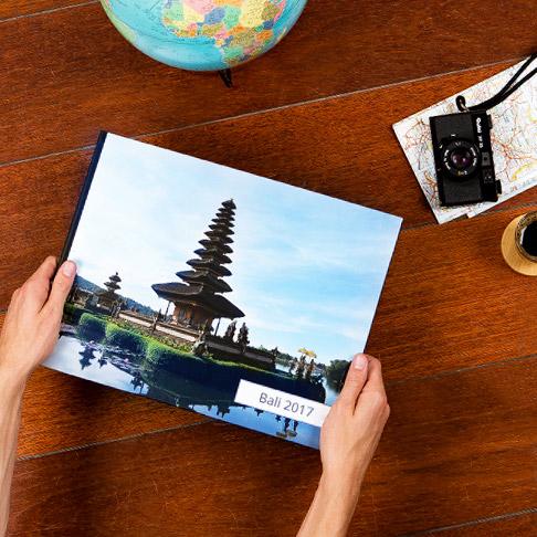 Reisefotobuch aus Bali auf einem Tisch mit einer Kamera im Hintergrund